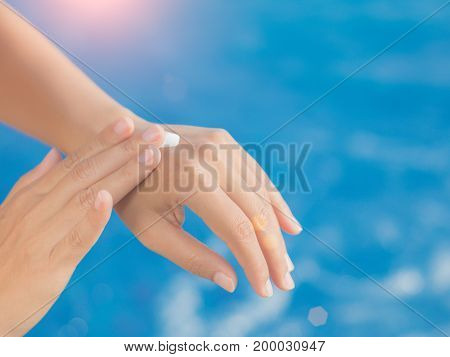 Woman hand apply sunscreen / sunblock by the swimming pool. Vacation and relaxation summer travel concept.