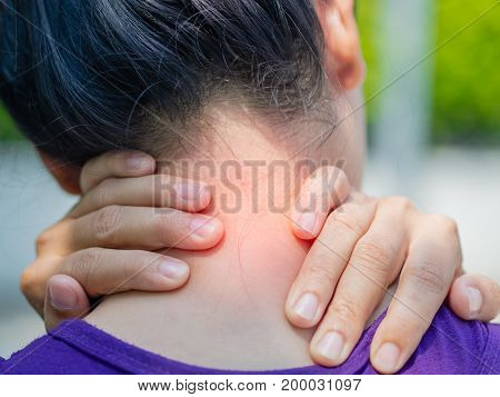 Athletic young woman touching her neck by painful injury over a nature background. Sport injuries concept.