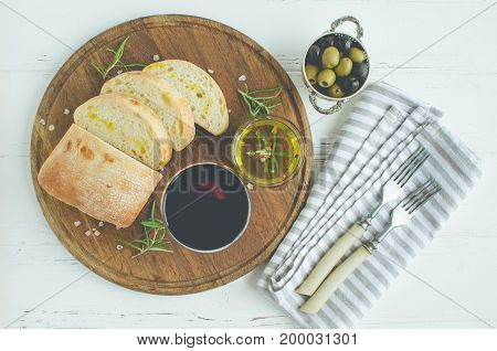 Wine snack set. Glass of red wine green and black mediterranean olives sliced ciabatta bread on wooden board over white table. Italian food concept. Top view.