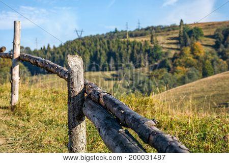 Wooden Fence On Hillside Near Forest