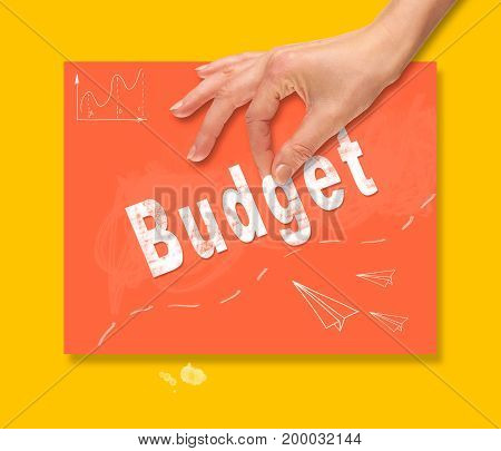 A Hand Picking Up A Budget Concept On A Colorful Drawing Board.