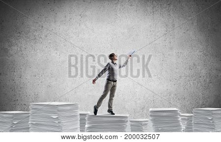 Man in casual wear keeping hand with book up while standing on pile of paper documents with grey background. Mixed media.
