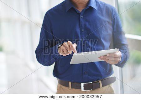 Hands of businessman using application on digital tablet