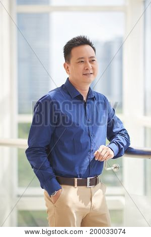 Smiling pensive Asian businessman looking through the office window