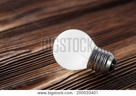 White Light Bulb Glowing On Wooden Background, Idea Concept