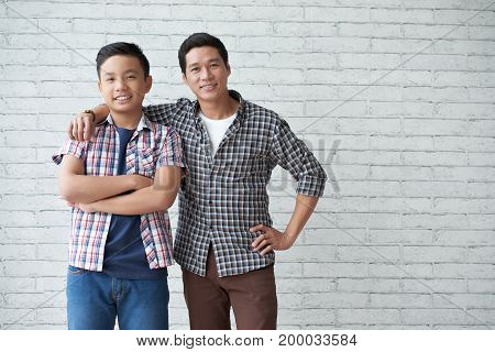 Happy mature Asian man and his cheerful teen son standing at white brick wall