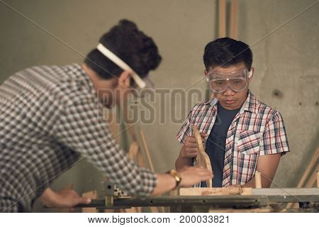 Asian mature man explaining his teen son how to saw wooden planks