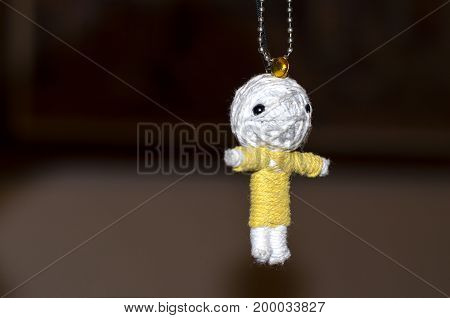 Cute little doll isolated on black background. Charm keychain for a children bag. Kids sewing crafts idea