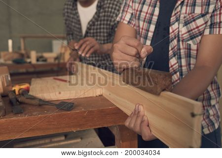 Carpenter apprentice using plane when working with wood