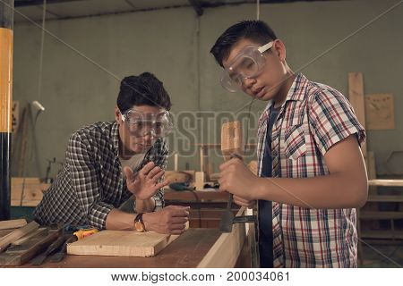 Teenage boy and his father working on new project in joinery