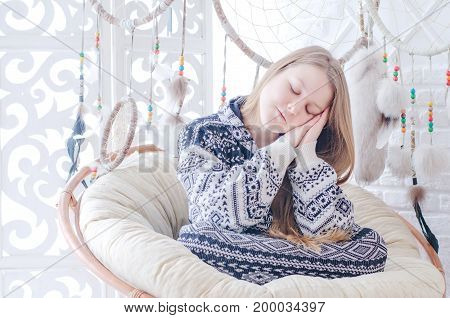 Blond Girl In Casual Clothes And Wool High Socks Sitting In A Cozy Rattan Arm-chair With Dream-catch