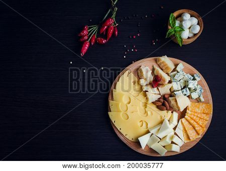 Cheese plate: Parmesan cheddar gouda mozzarella and other with chili pepper and almonds on wooden board with place for text. Tasty appetizers. Top view. Copy space.