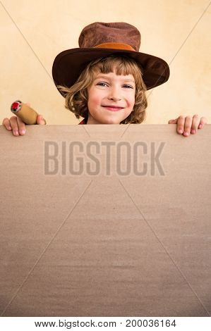 Funny cowboy kid holding banner blank with copy space