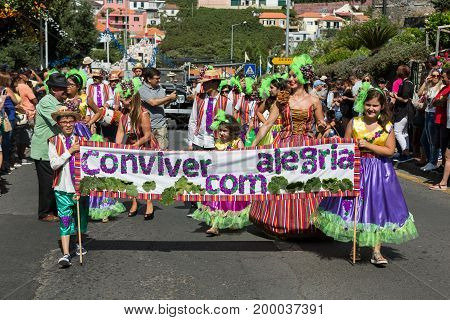 ESTREITO DE CAMARA DE LOBOS PORTUGAL - SEPTEMBER 10 2016: People wearing in colorful costumes at Madeira Wine Festival in Estreito de Camara de Lobos Madeira Portugal. The Madeira Wine Festival honors the grape harvest with a celebration of traditional lo