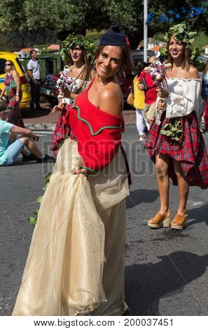 ESTREITO DE CAMARA DE LOBOS PORTUGAL - SEPTEMBER 10 2016: Woman wearing in traditional costumes at Madeira Wine Festival in Estreito de Camara de Lobos Madeira Portugal. The Madeira Wine Festival honors the grape harvest with a celebration of traditional