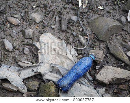 Blue plastic bottle on the garbage dump.