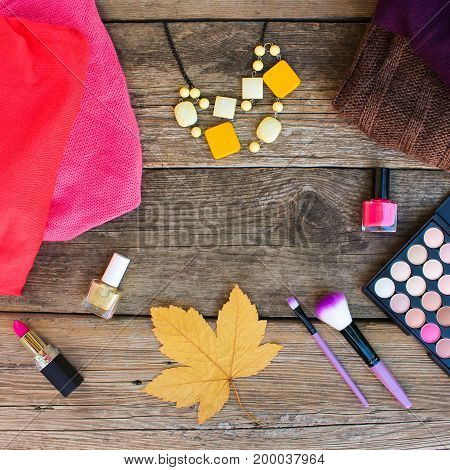 Women's clothing and cosmetics: sweaters, lipstick, nail polish, necklaces, eye shadow, brushes, yellow leaves on wooden background. Top view. Toned image.