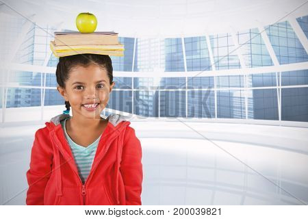 Smiling girl balancing books and apple on head against modern room overlooking city