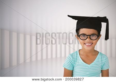 Portrait of cheerful girl wearing eyeglasses and mortarboard against white curved room