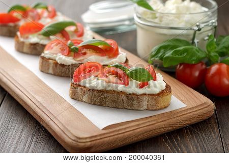 Bruschetta With Cheese Feta, Tomatoes And Basil On Wooden Cuttin Board.
