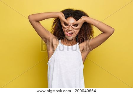Fun and People Concept - Headshot Portrait of happy Alfo African American woman with freckles smiling and making finger glasses. Pastel yellow studio background. Copy Space.