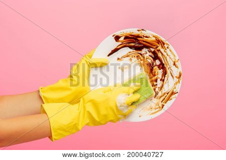 Hands in yellow protective gloves washing a plate against rose background