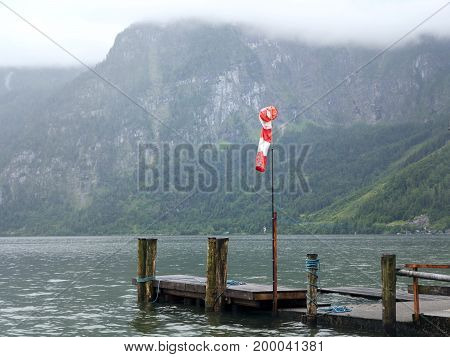 Mountain lake with small wooden jetty, pier mole, wind sleeve. Alpine tarn, beautiful canyon in Austria. Valley in summer, clear water. Virgin mountain nature. Salzburg vacation landscape, Hallstatt.