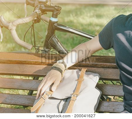 Unrecognizable young man with backpack and bicycle rests on wooden bench in summer park.