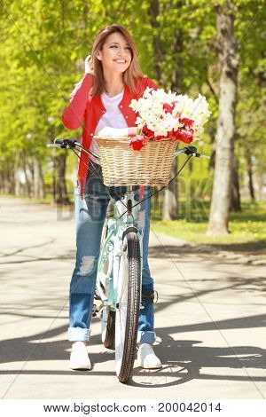 Young beautiful girl with bicycle in park on sunny day