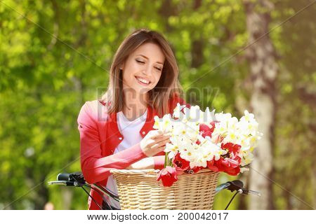 Young beautiful girl and bicycle with flowers in basket at park on sunny day