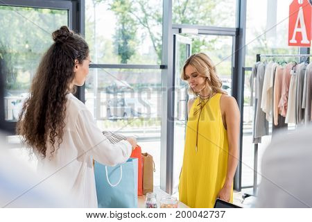 Cashier Packing Clothes Of Beautiful Blonde Woman In Paper Bags