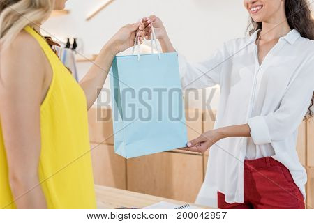 Cropped Shot Of Cashier Giving Shooping Bag To Beautiful Female Customer