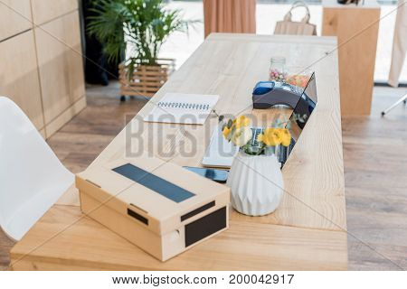 cash desk with shoe box and laptop in clothes store