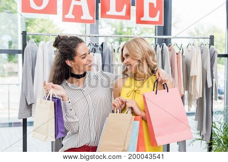 Young Beautiful Women With Bags In Clothes Store