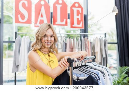 Beautiful Shopaholic Blonde Woman Leaning On Rack In Clothes Store