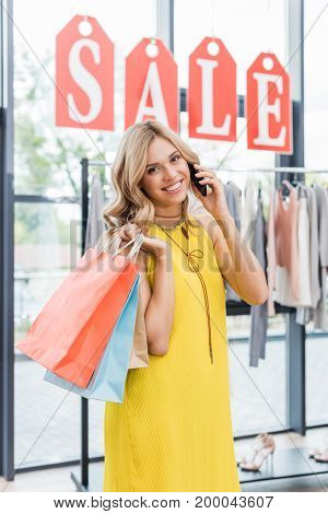 Young Blonde Woman In Clothes Store Laking By Phone