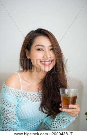 Beautiful Young Asian Woman Drinking Her Morning Tea Over A Breakfast At Home.