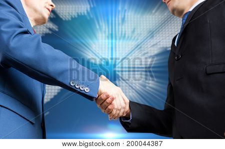 Businessman shaking hands against glowing world map on black background