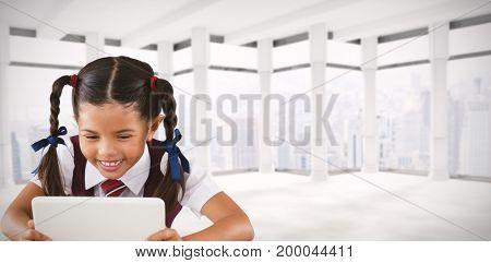 Schoolgirl using digital tablet at desk against windows overlooking city