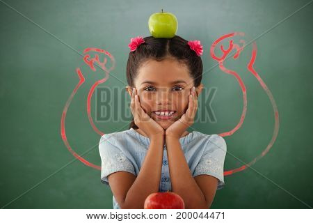 Girl with Granny Smith apple on head against green chalkboard