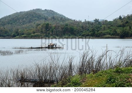 A fisherman works in his boat-house over Samorthong reservoir UthaiThani Thailand