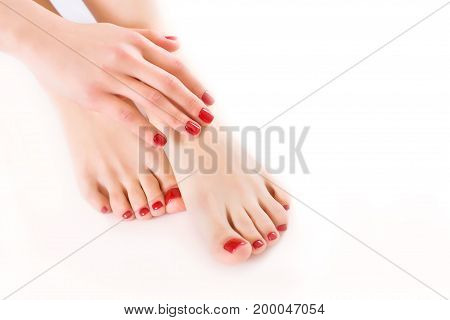 Well-groomed hands and feet on a white background close-up.