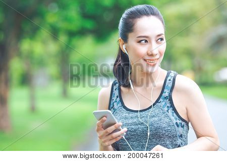 Fitness Woman Is Listening To Music From Her Mobile Phone While Running In The Park.