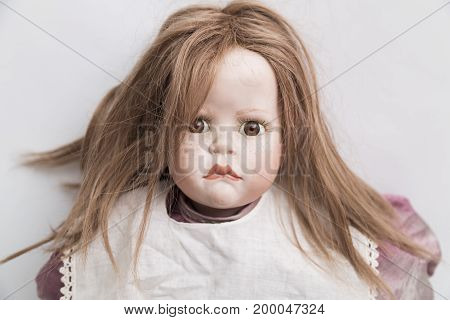 Portrait of ceramic porcelain handmade vintage doll with long blond hair in an old violet linen dress and white apron on white background.