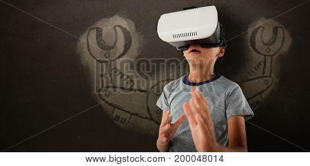 Boy gesturing while using virtual reality headset against blackboard