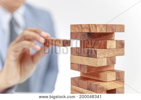 businessman building tower of wooden blocks on white background