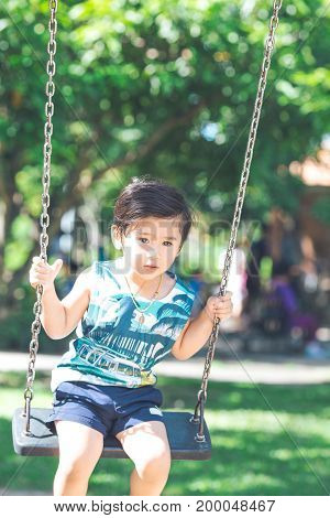 A Cute Asian Boy Is Playing Swings Happily In The Park.