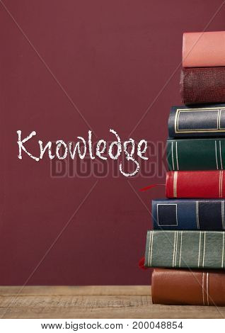 Digital composite of Books on the table against red blackboard with knowledge text