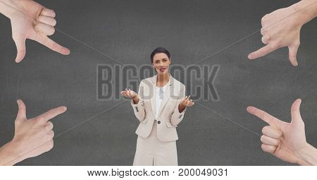 Digital composite of Hands pointing at confused business woman against grey background