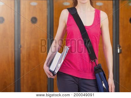 Digital composite of female student holding books in front of lockers